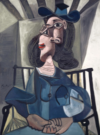 Girl in a hat seated in an armchair