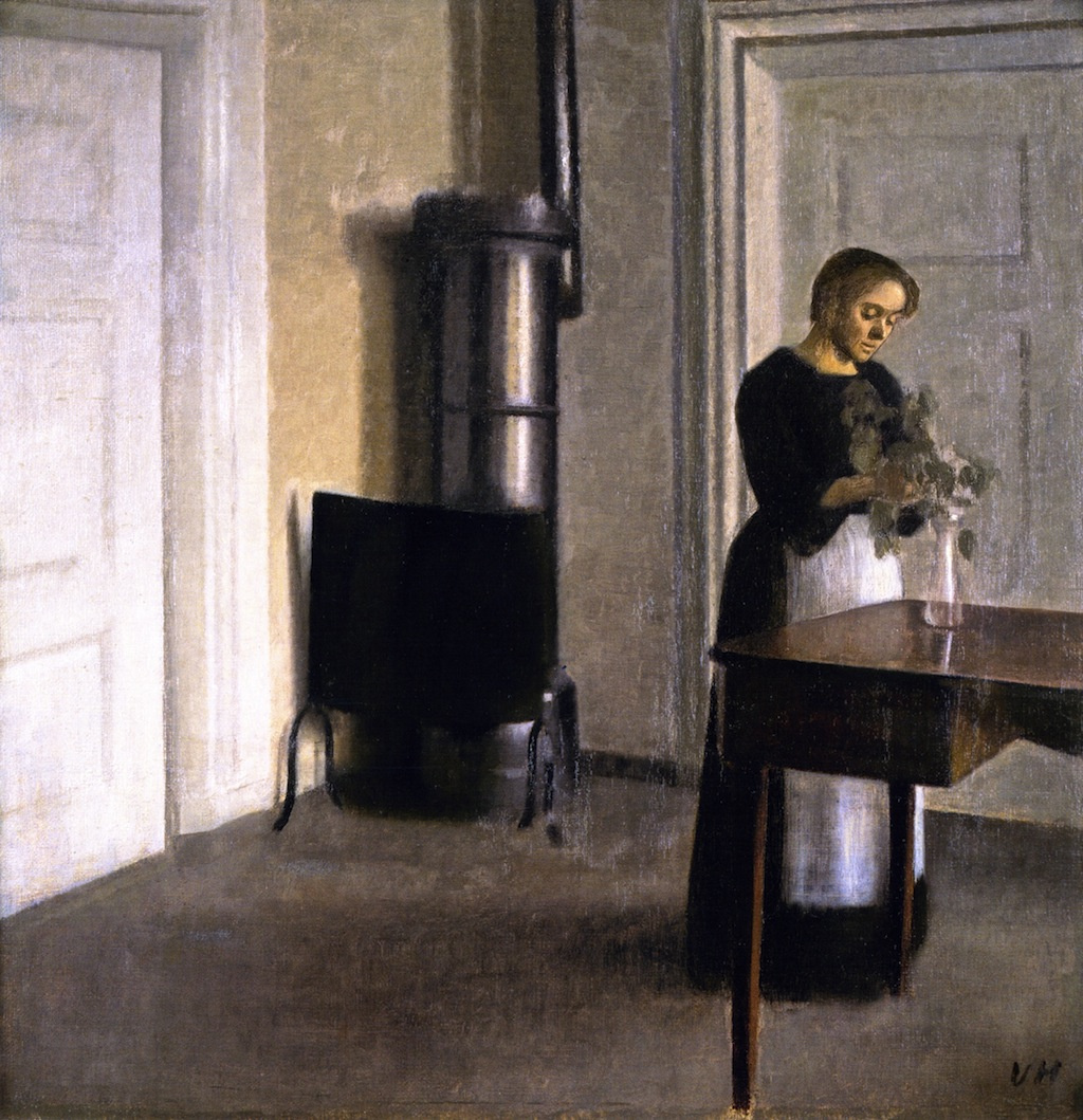 Vilhelm Hammershøi. Interior with a young woman. Ida putting flowers in a glass vase