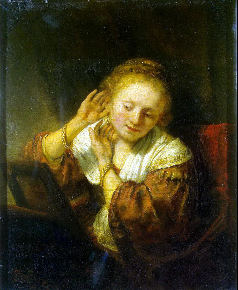 Рембрандт Харменс ван Рейн. Молодая женщина, примеряющая серьги