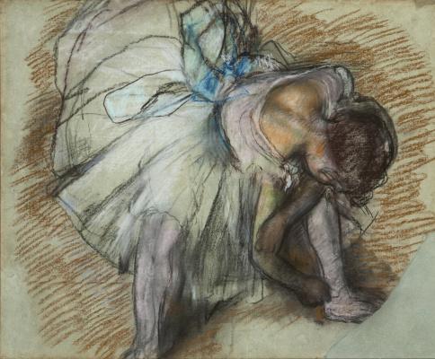 Сидящая балерина, завязывающая ленты балетных туфель
