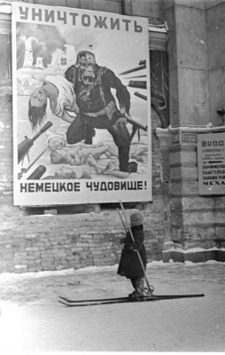 "Historical photos. A child on the street of besieged Leningrad at the poster ""Destroy the German Monster!"". Winter 1941-1942."