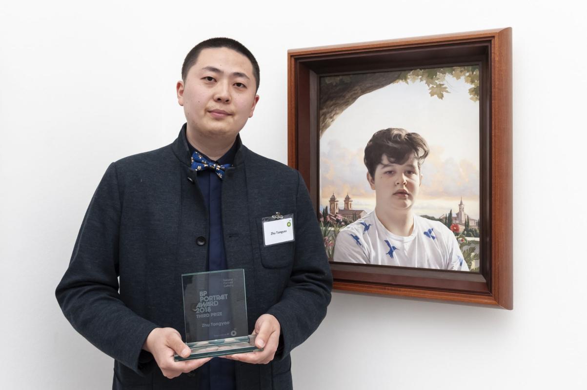 Чжу Тунъяо рядом с портретом «Саймон».Фото: creativeboom.com