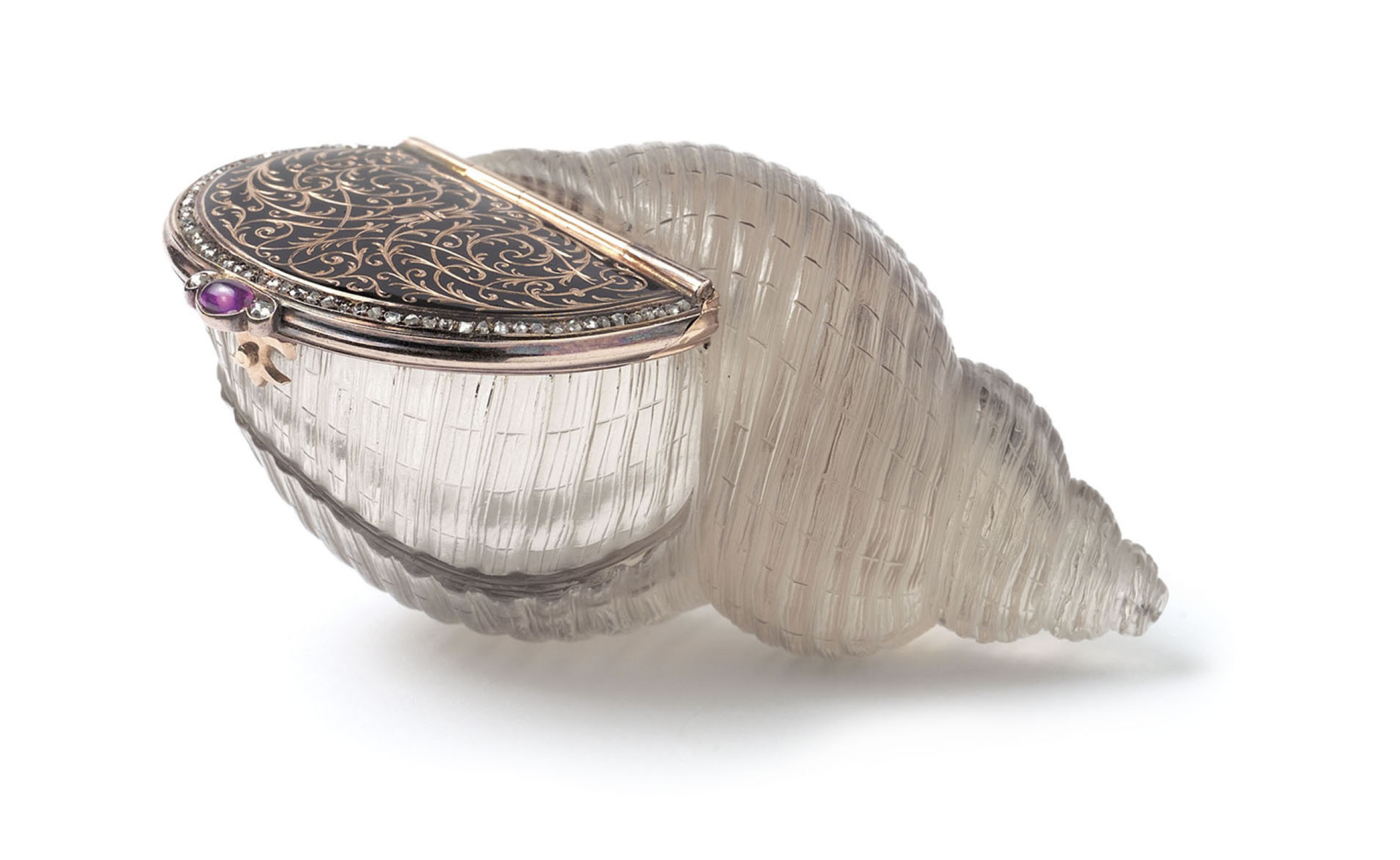 The shell-shaped enamel bonbonniere cut from solid topaz with hinged lid. The lid is inlaid with gol