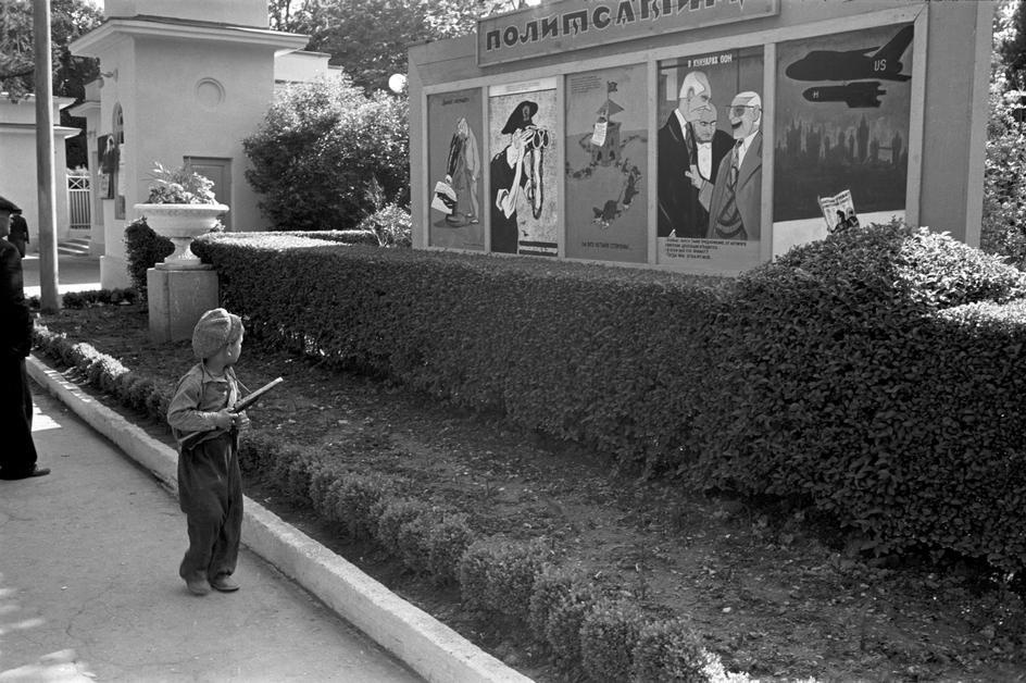 Historical photos. Propaganda posters in Moscow. The boy considers street caricatures on topical topics