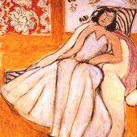 Женщина в кресле на охристом фоне