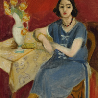 Женщина в голубом у стола на красном фоне